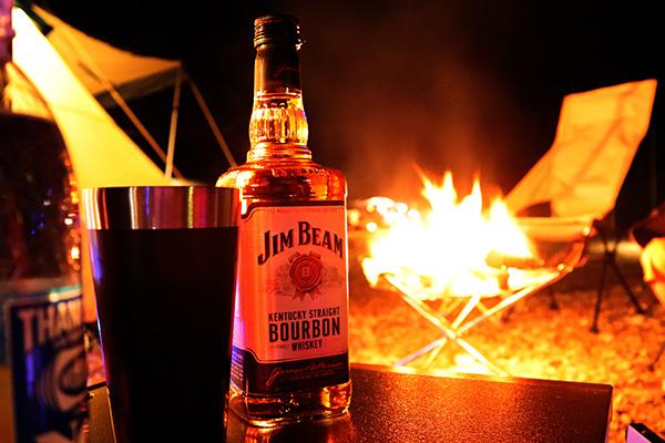 バーボンのボトルと焚火