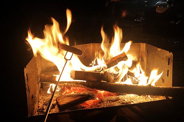 焚き火でウインナーを焼く