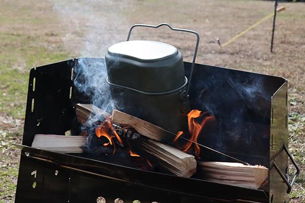 薪グリルの焚き火に飯盒を突っ込む